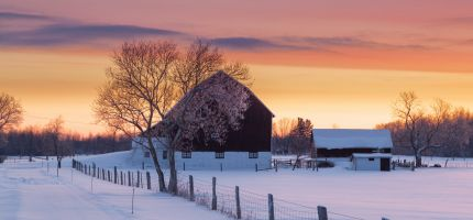 Snowy barn with sunset